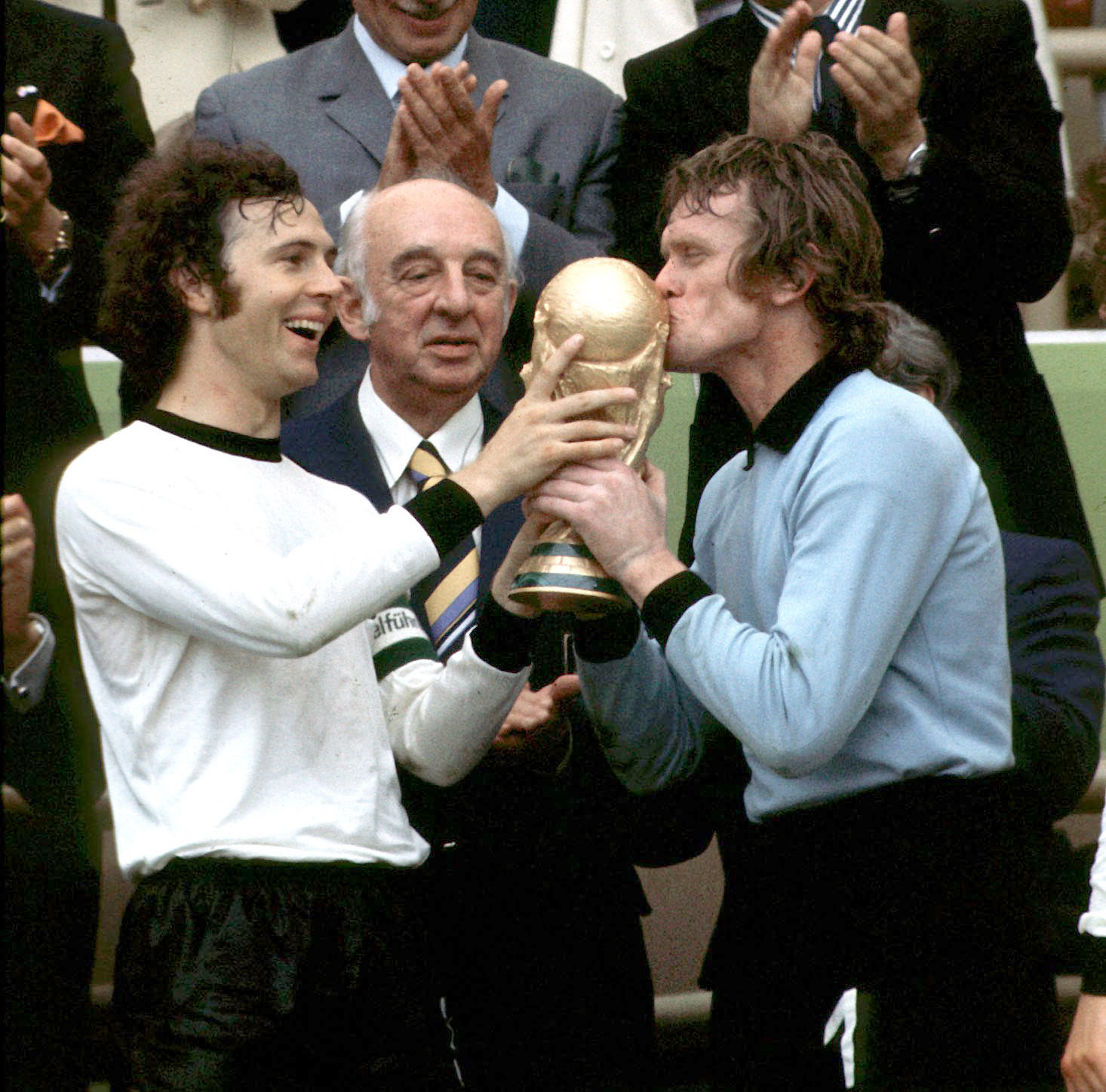 Laughing team captain Franz Beckenbauer is holding the conquered World Cup trophy and goalkeeper Sepp Maier is kissing the trophy. DFB president Hermann Goessmann is watching. Sep Majer i Franc Bekenbauer 1974 FIFA World Cup final 2:1 against Netherlands in Munich's Olympic stadium in Germany